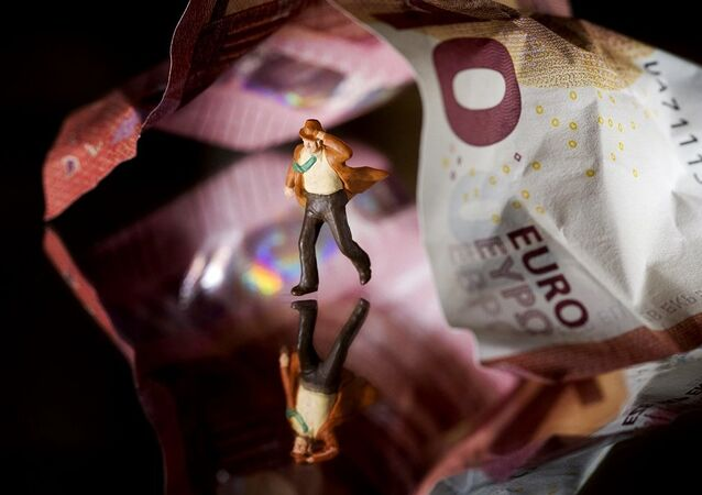 This illustration picture taken in Paris on July 7, 2015 shows a plastic figurine set in the motion of running from underneath a 10 Euro note.