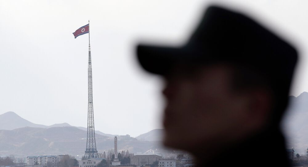 A South Korean soldier stands as a North Korean flag flutters in the wind atop a 160-meter (533-foot) tower in the village of Gijungdong near the north side of the border village of Panmunjom, which has separated the two Koreas since the Korean War, in Paju, north of Seoul, South Korea, Wednesday, Nov. 12, 2014