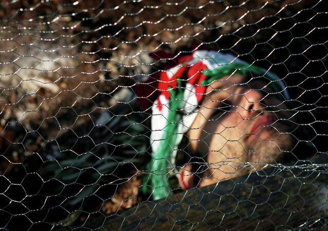 An Israeli activist lays behind wire fencing as he and others try to stop Israeli bulldozers, not seen, from working, during a joint protest with Israelis, Palestinians and foreign peace activists against Israel's seperation barrier in the West Bank.