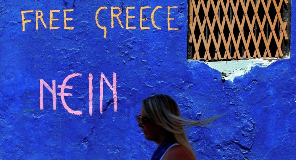 A tourist passes a graffiti in the Plaka tourist district of Athens, Greece
