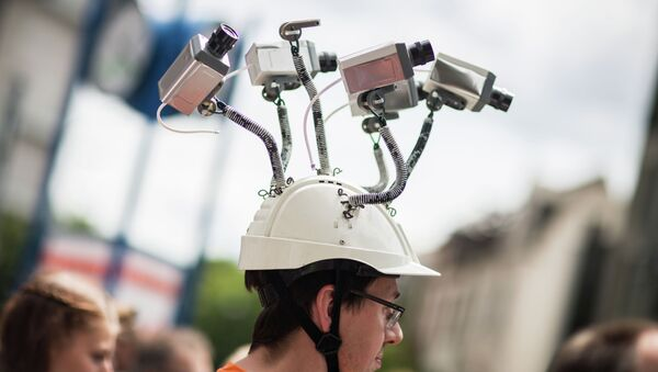Chairman of Hesse's Pirate Party Volker Berkhout wears a hat with mock surveillance cameras during a demonstration against spying activities of the US intelligence agency NSA and its German partner service BND in Frankfurt am Main, central Germany, on May 30, 2015 - Sputnik International