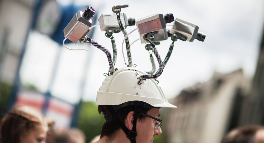 Chairman of Hesse's Pirate Party Volker Berkhout wears a hat with mock surveillance cameras during a demonstration against spying activities of the US intelligence agency NSA and its German partner service BND in Frankfurt am Main, central Germany, on May 30, 2015