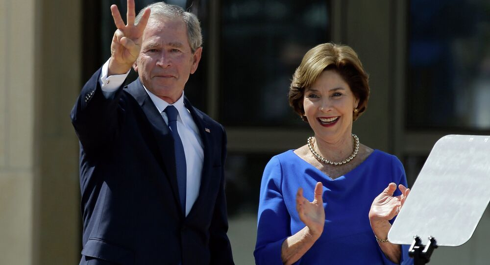 Former President George W. Bush, accompanied by his wife former first lady Laura Bush, flashes the W sign after his speech during the dedication of the George W. Bush Presidential Center
