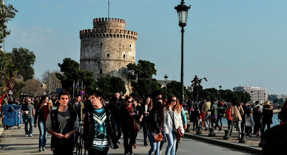 People walk at a main seaside avenue, as the White Tower is seen at the background, in the Greek northern town of Thessaloniki, Greece.