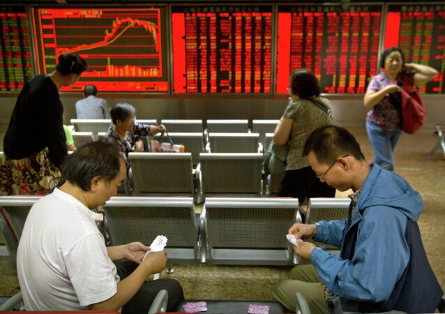 Chinese investors play cards as they sit in a brokerage house in Beijing, Friday, July 10, 2015