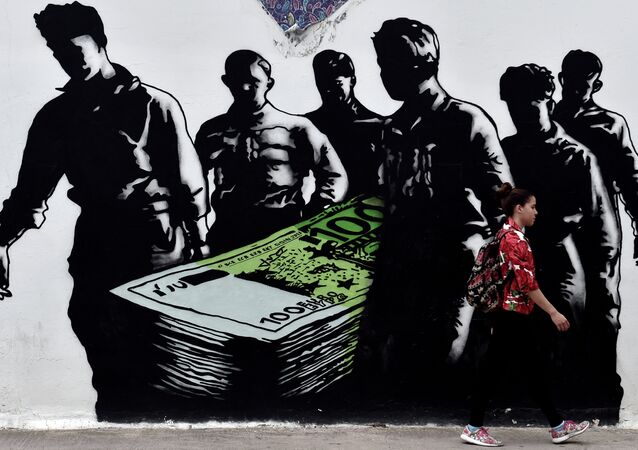 A young woman walks past a graffiti called 'Death of Euro' by French street artist Goin, in central Athens on June 19, 2015