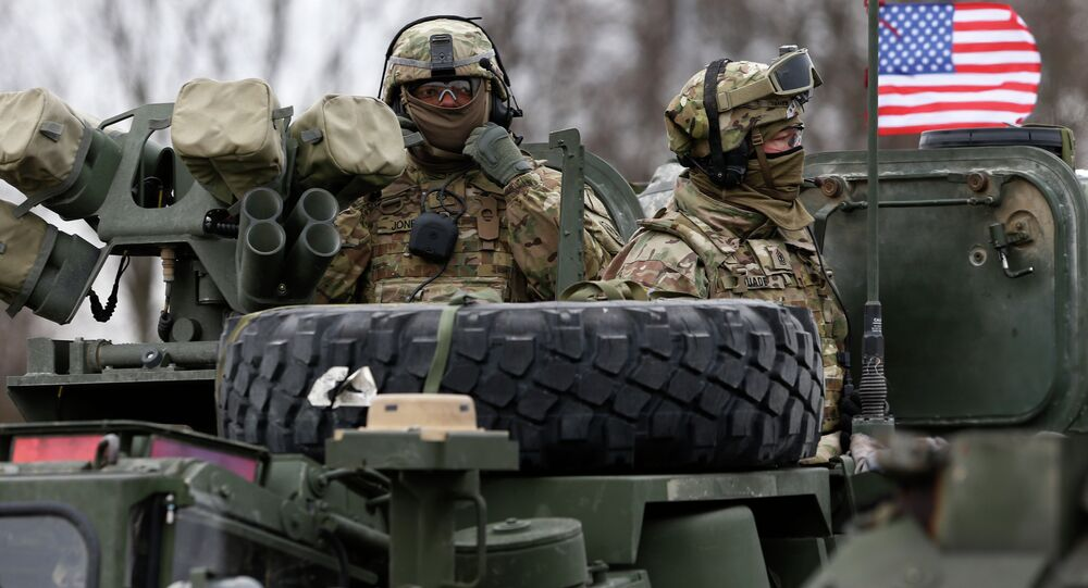 Members of US Army's 2nd Cavalry Regiment ride on an armored vehicle during the ''Dragoon Ride'' military exercise in Salociai some 178 kms (110 miles) north of the capital Vilnius, Lithuania, Monday, March 23, 2015