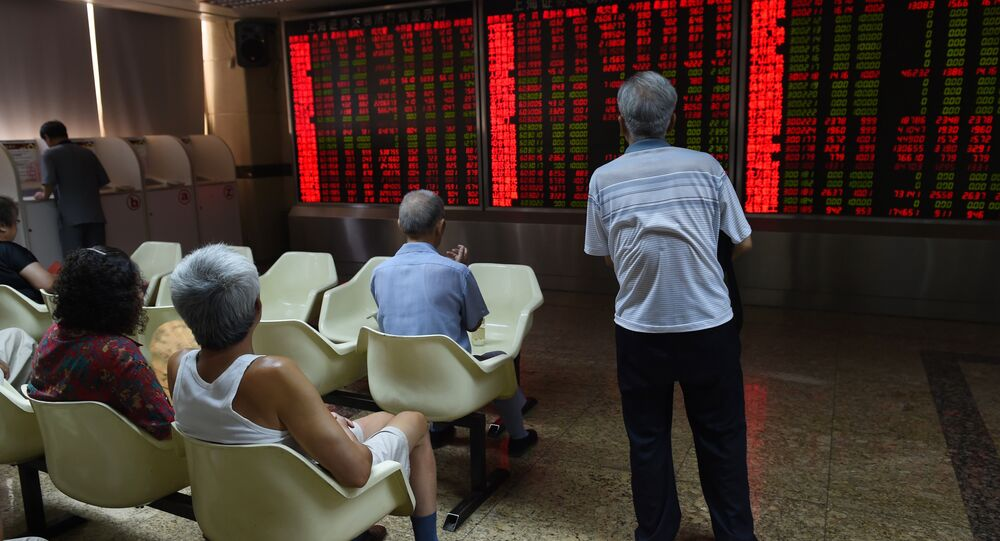 Investors look at a board showing stock market movements at a securities company in Beijing on July 10, 2015