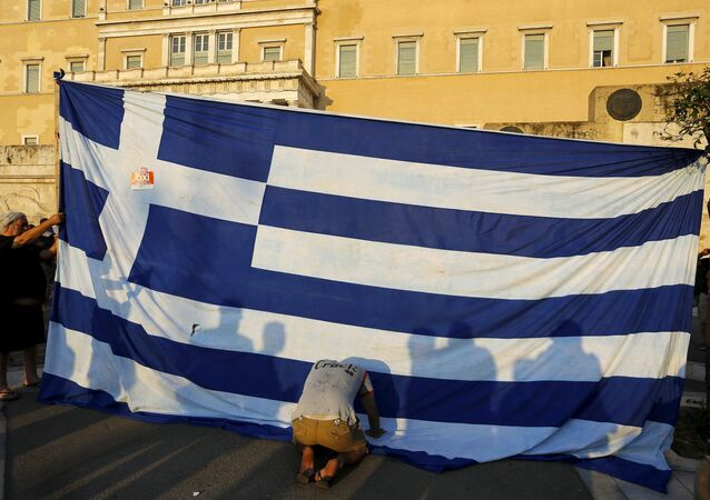 A protester kneels to pay his respect in front of a Greek flag during an anti-austerity rally in Athens, Greece, June 29, 2015