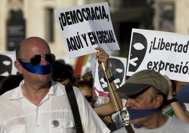 Demonstrators with their mouths taped attend a protest against Spanish government's new security law in central Madrid, Spain, June 30, 2015