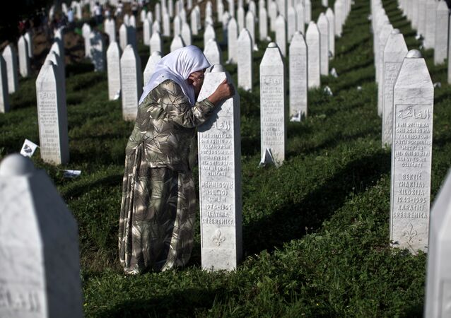 A woman weeps as she visits the grave of a family member at the Potocari memorial complex near Srebrenica, 150 kilometers (94 miles) northeast of Sarajevo, Bosnia and Herzegovina, Saturday, July 11, 2015
