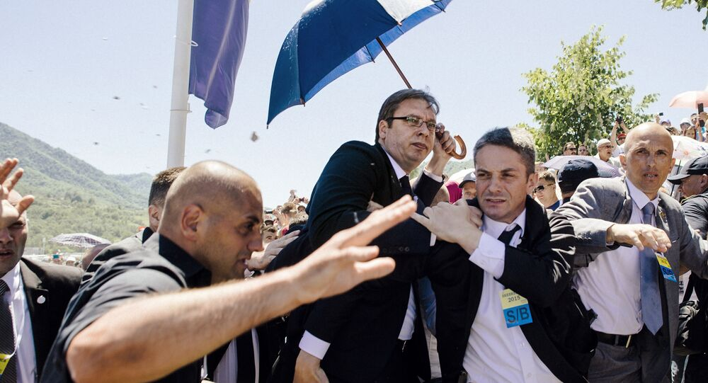 Bodyguards try to protect Serbian Prime Minister Aleksandar Vucic (C) from stones hurled at him by an angry crowd at the Potocari Memorial Center, near the eastern Bosnian town of Srebrenica on July 11, 2015