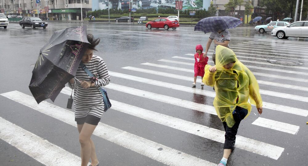 Pedestrians hold their umbrellas against strong wind as Typhoon Chan-Hom hits Shanghai, China, July 11, 2015