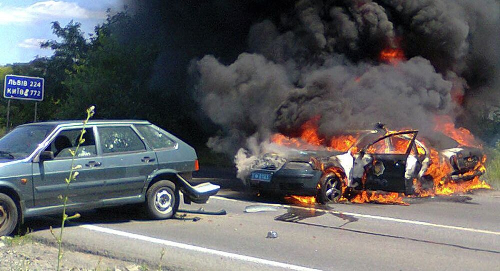 Two police cars on fire are seen at the site of unrest in Mukhachevo, Western Ukraine, Saturday, July 11, 2015