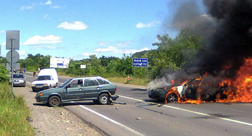 A police car is seen on fire at the site of unrest in Mukachevo, Western Ukraine, Saturday, July 11, 2015