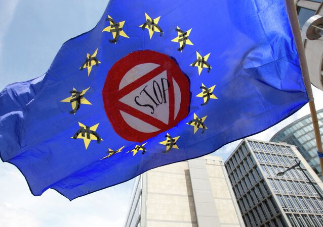 A flag which says stop and has euro money signs in the EU stars flaps in the wind during a protest march in solidarity with Greece in the center of Brussels on Sunday, June 21, 2015
