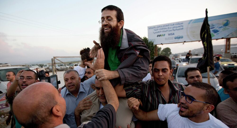 Palestinian Khader Adnan, center, is greeted by Palestinians after his release from an Israeli prison in the West Bank village of Arrabeh near Jenin, Sunday, July 12, 2015