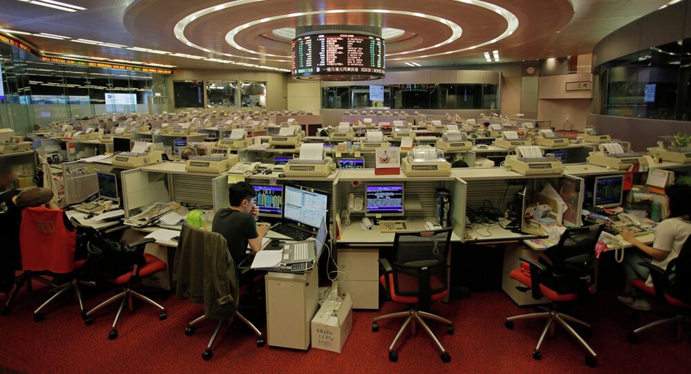 In this June 10, 2015 photo, traders work at Hong Kong's Stock Exchange in Hong Kong