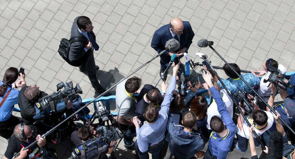 European Commissioner for the Economy Pierre Moscovici, center, speak with the media as he arrives for a meeting of eurozone finance ministers in Brussels on Thursday, June 25, 2015