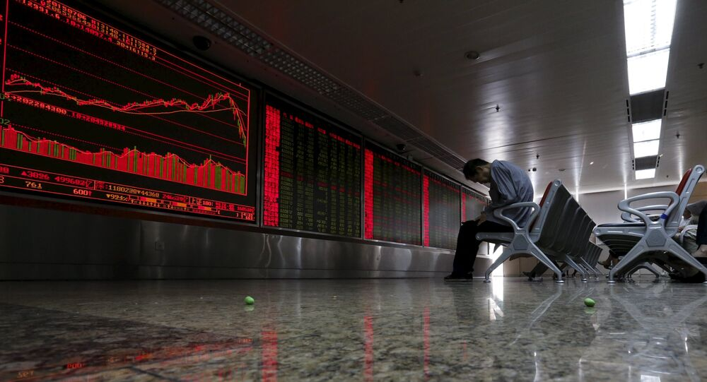 An investor takes notes as he watches a board showing stock prices at a brokerage office in Beijing, China, in this July 6, 2015 file photo