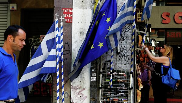 A woman looks at sandals from a shop as an a man passes by Greek and European Union flags in central Athens, Wednesday, July 8, 2015 - Sputnik International