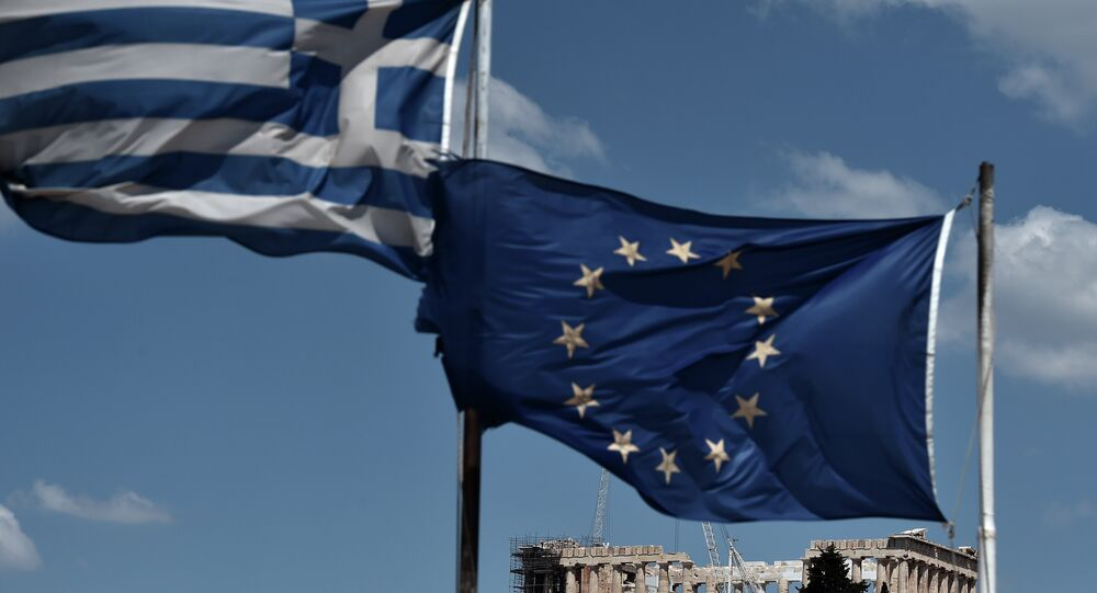An EU and a Greek flag wave above the ancient temple of Parthenon atop the Acropolis hill in Athens on July 7, 2015