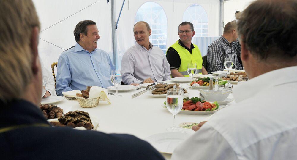 Prime Minister Vladimir Putin (second left, background) and German ex-Chancellor Gerhard Schroeder