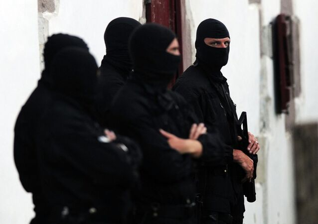 Police officers stand guard outside of a house after arresting two presumed member of the armed Basque separatist group Euskadi Ta Askatasuna (ETA) in Osses on July 7, 2015.