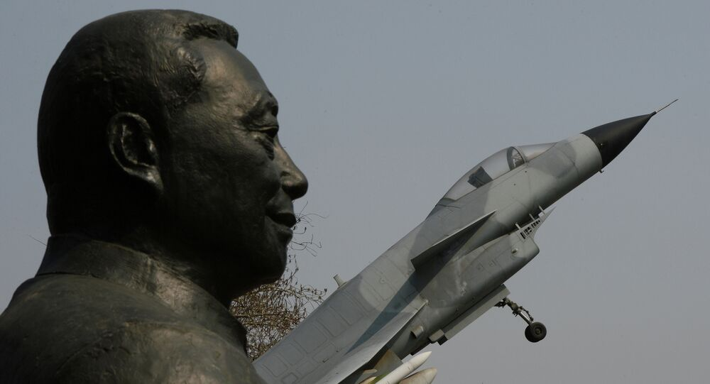 A statue of Wu Daguan who is known as the 'Father of China's military and civilian aviation industry' beside a Chinese produced J-10 fighter jet in Beijing