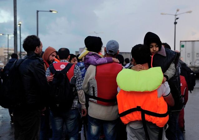 Temporary detained migrants walk at the port at Greek island of Kos