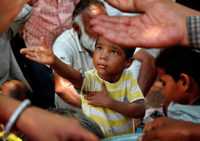 A child stretches arms to receive free food