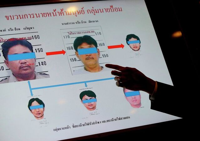 An official from Thailand's Department of Special Investigation points at a chart showing suspects in a human trafficking ring during a news conference in Bangkok, Thailand, Wednesday, July 1, 2015.