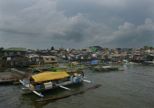 Fishing outrigger boats are anchored at the mouth of a river feeding Manila Bay, as the Philippine coast guard banned sailing due to nearby Typhoon Noul in the northern part of the country