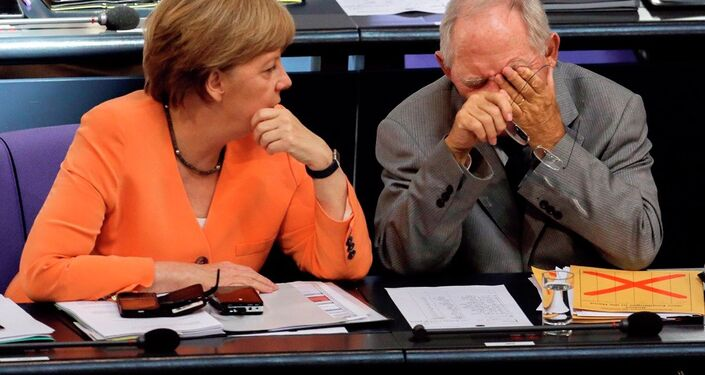 German Chancellor Angela Merkel, left, talks to Finance Minister Wolfgang Schaeuble during a debate on the Greek financial crisis at the German parliament in Berlin, Wednesday, July 1, 2015.