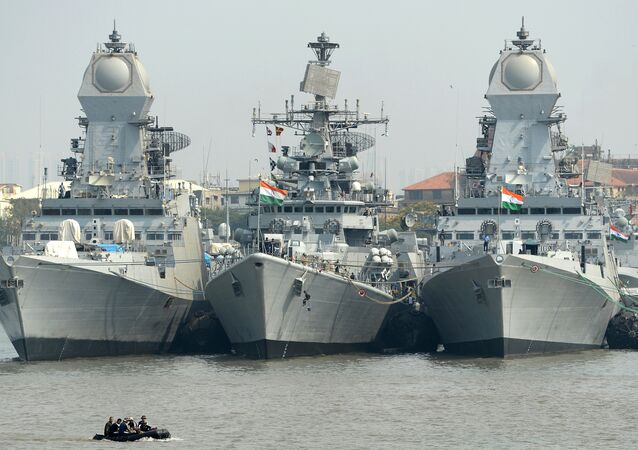 Indian naval sailors on a rubber inflatable boat pass naval warships at the Naval Dockyard in Mumbai
