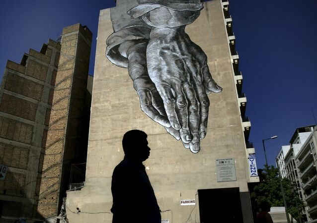A pedestrian walks through empty streets by a mural in Athens, Greece