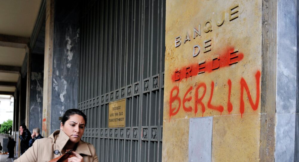 A woman passes by the Bank of Greece headquarters where 'Greece' was changed to 'Berlin' during a 24-hour general strike in Athens on February 7, 2012.