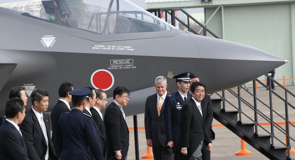 Japan's Prime Minister Shinzo Abe, right, looks at a mock-up of F-35 fighter jet.