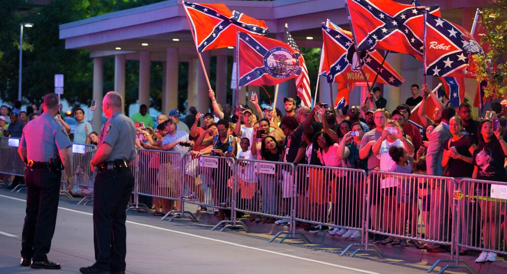 People wave Confederate flags outside the hotel that President Barack Obama is staying the night, on Wednesday, July 15, 2015, in Oklahoma City. Obama is traveling in Oklahoma to visit El Reno Federal Correctional Institution.