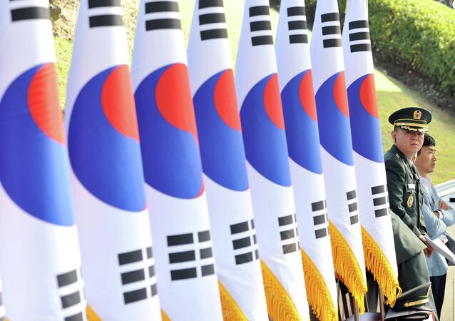 A South Korean military officer (R) stands next to a line of national flags during a ceremony to mark the 64th Korea Armed Forces Day at the military headquarters in Gyeryong, about 140 km south of Seoul, on September 25, 2012