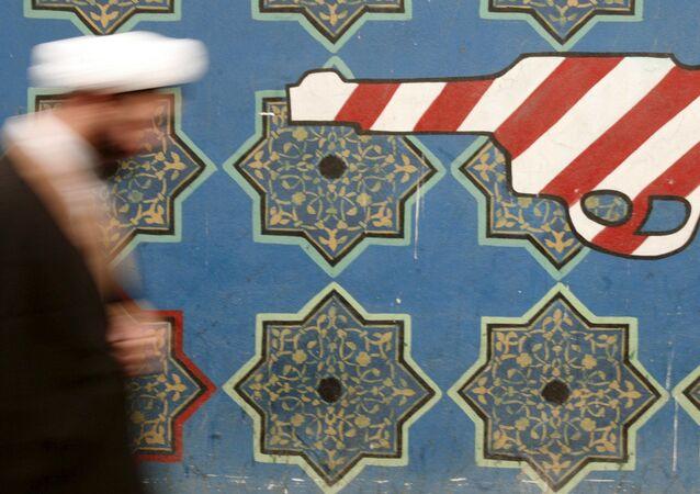 Иранский священнослужитель проходит мимо росписи на стене бывшего посольства США в Тегеране