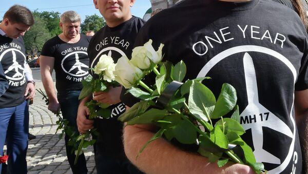 People wearing t-shirts bearing a drawing of a plane and slogans reading  MH 17, One year in the skies hold flowers to the Dutch embassy in Kiev on July 17, 2015 in memory of the people who died in the crash of Malaysian Airlines flight MH17 - Sputnik International