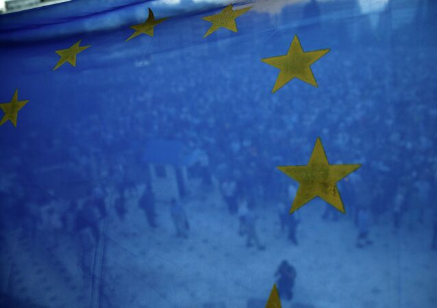 Protesters are seen through a European Union flag during a rally in front of the parliament in Athens, Greece, on Thursday, June 18, 2015