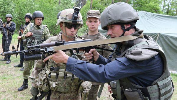 US Sgt Barrett, left, instructs a Ukrainian soldier during joint training exercises on the military base in the Lviv region, western Ukraine, Thursday, May 14, 2015 - Sputnik International