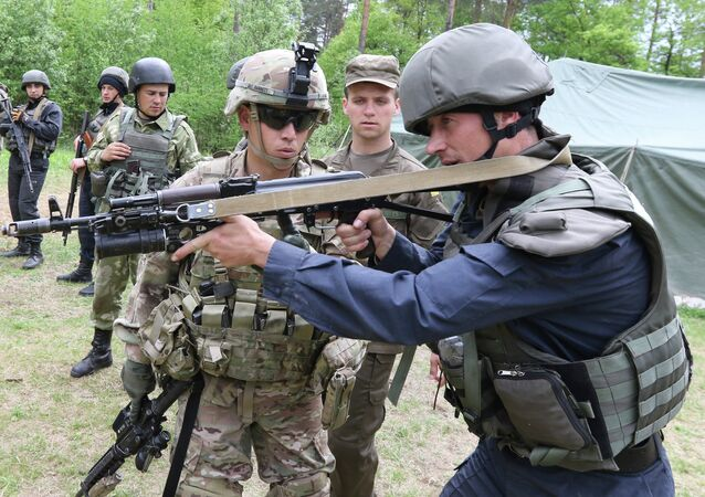 US Sgt Barrett, left, instructs a Ukrainian soldier during joint training exercises on the military base in the Lviv region, western Ukraine, Thursday, May 14, 2015