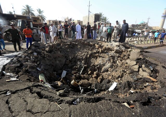 Iraqi men look at a crater left by a massive suicide car bomb attack carried out the previous day by the Islamic State group in the predominantly Shiite town of Khan Bani Saad, 20 km north of Baghdad, on July 18, 2015.