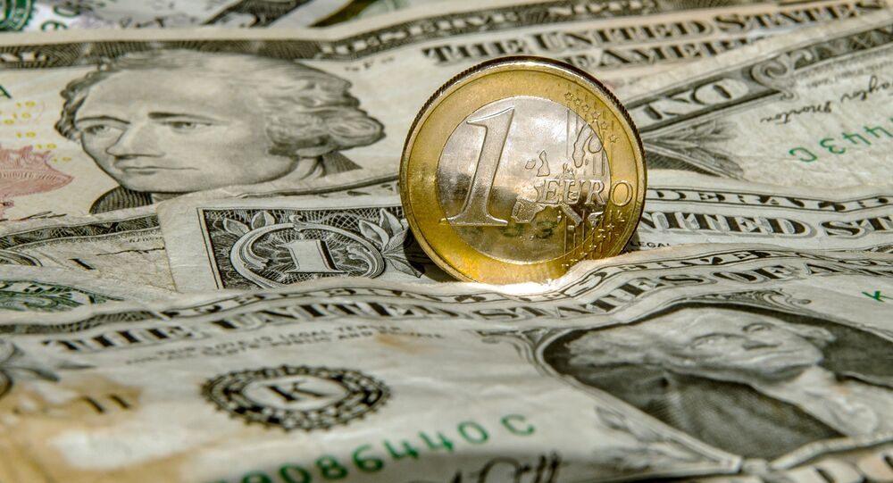 A one euro coin is pictured on one US dollar notes on March 13, 2015 in Godewaersvelde, Northern France
