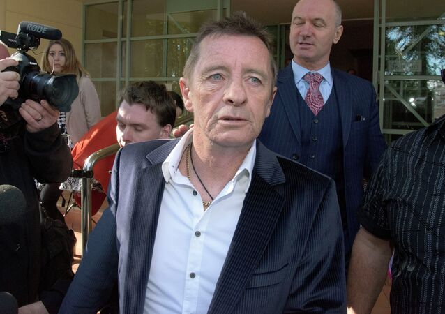 Former AC/DC drummer Phil Rudd (C) leaves the District Court after being sentenced to 8 months home detention in Tauranga, New Zealand on July 9, 2015