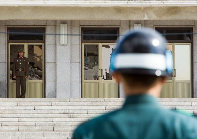 A South Korean JSA guard (front R) and North Korean guard (L) stand guard opposite each other at the border of the truce village of Panmunjom in the Demilitarized zone (DMZ) dividing the two Koreas. File photo.