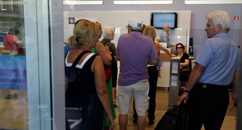 Customers wait to be served inside an Alpha Bank branch in Athens, Monday, July 20, 2015